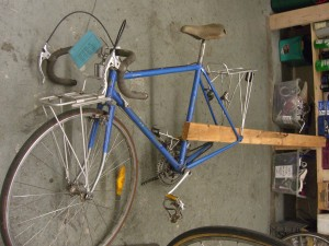 Using a 2x4 to spread the bike's rear triangle. (Do not attempt with anything but a steel frame bike)